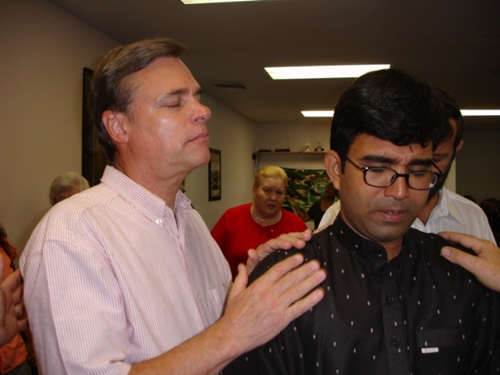 Photo of Ken praying with a client